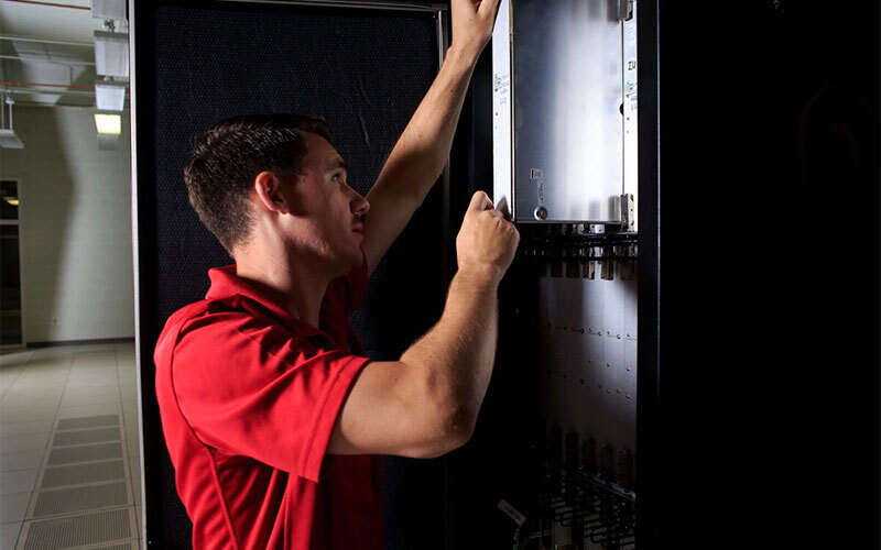 Man repairing a supercomputer in IU's data center