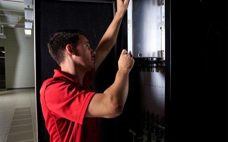 Man repairing a supercomputer in IU's data center