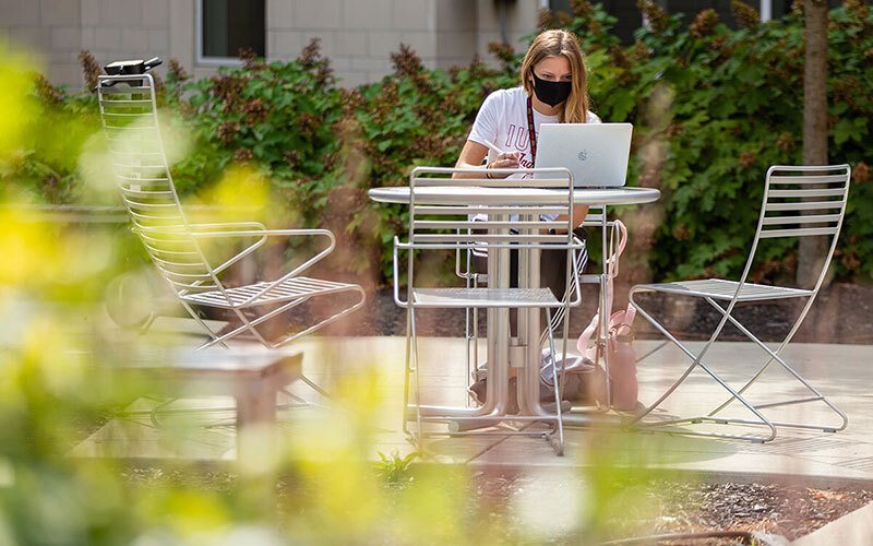 Woman at outdoor table with open laptop on the IU Bloomington campus
