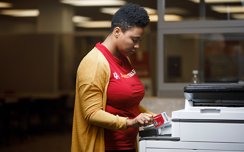 A woman swiping her Crimson Card to access a printer.
