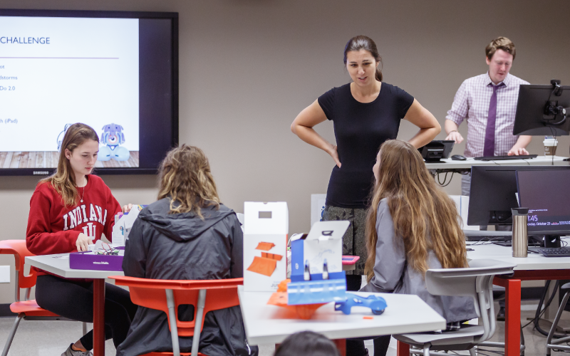 An instructor speaks to students seated at a table