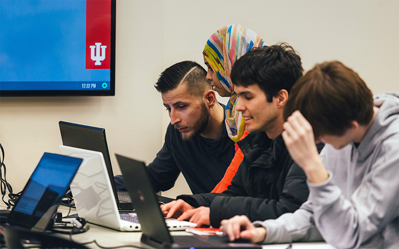 Students on laptops with instructor observing in IUPUI classroom