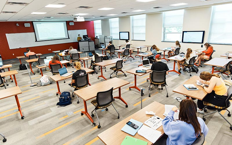 Classroom with students distanced and instructor teaching at front in Teter Hall on IU Bloomington campus.